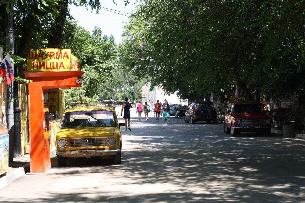 Автомобили вдоль набережной и на привокзальной площади Феодосии
