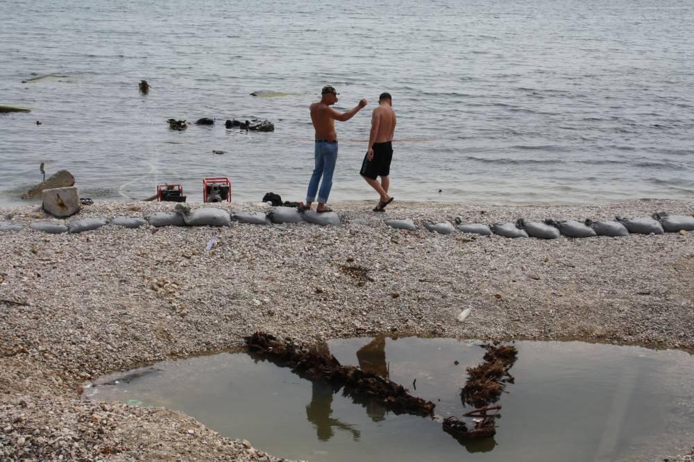 Разбирают остатки корабля на мелководье центрального пляжа Феодосии